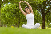 Healthy woman stretching hands in park — Stock Photo