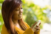 Beautiful woman text messaging in park — Stock Photo