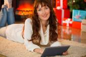Redhead woman lying on floor using tablet at christmas — Stock Photo