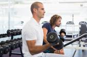 Side view of men exercising with dumbbells in gym — Foto de Stock