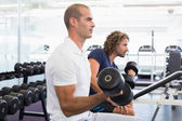 Side view of men exercising with dumbbells in gym — ストック写真
