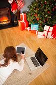 Pretty woman lying on floor using technology at Chritmas — Stock Photo