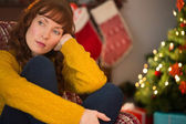 Beauty red hair thinking on the armchair at christmas — Stock Photo