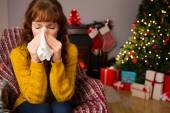Woman sitting on sofa and blowing her nose at christmas — Stock Photo