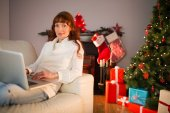 Smiling redhead woman using laptop on couch at christmas — Stock Photo