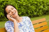 Smiling brunette sitting on bench phoning — Stock Photo