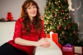 漂亮的红发在圣诞节在沙发上摆姿势 — 图库照片