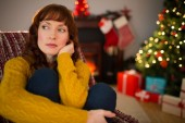 Pretty redhead thinking on the armchair at christmas — Foto de Stock