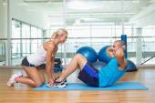 Trainer assisting young man with abdominal crunches at fitness s — Stock Photo