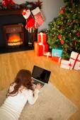 Redhead woman lying on floor using laptop at christmas — Stock Photo