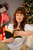 Веселый рыжая, сидя на полу чтения — Стоковое фото