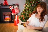 Relaxed redhead reading on the couch at christmas — Foto de Stock