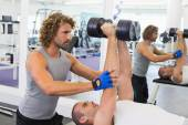 Male trainer assisting man with dumbbells in gym — Stock Photo