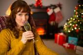 Pretty redhead drinking glass of champagne on couch — Stock Photo