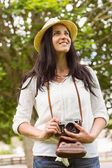 Smiling brunette holding old fashioned camera — Stock Photo