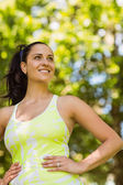 Smiling brunette in sportswear with her hands on hips — Stock Photo