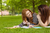 Female students with books in park — Stock Photo