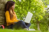 Młoda kobieta korzysta z laptopa w parku — Zdjęcie stockowe