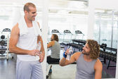 Smiling trainer talking to fit man at gym — Stock Photo