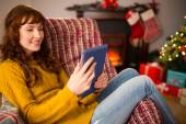 Redhead woman sitting on couch using tablet at christmas — Foto de Stock
