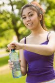 Woman holding water bottle in park — Stock Photo