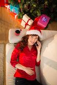 Redhead in santa hat lying on the sofa phoning — Photo