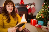 Cheerful red hair reading a book at christmas — Stock Photo