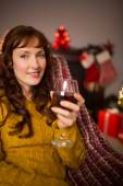 Woman sitting on a couch while holding a glass of red wine — ストック写真
