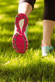 Woman in running shoes jogging on grass — Stock Photo