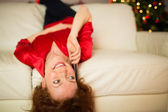 Happy redhead lying on the couch phoning — Stock Photo