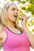 Fit blonde eating green apple — Stock Photo