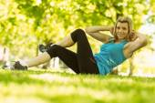 Fit blonde doing sit ups in the park — Stock Photo