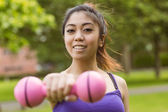 Woman lifting dumbbell in park — Stock Photo