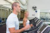 Side view of couple running on treadmills at gym — Stock Photo