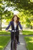 Pretty redhead cycling a bike — Stock Photo
