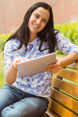 Smiling brunette sitting on bench using tablet — Stock Photo