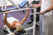 Trainer with clipboard besides woman lifting barbell in gym — Stockfoto