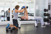 Male trainer assisting young man with dumbbells in gym — Stock Photo