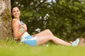 Fit brunette sitting against a tree holding her bottle — Stock Photo