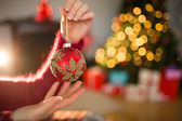 Woman in jumper holding red bauble — Stock Photo