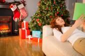 Glad rödhårig läsning i soffan vid jul — Stockfoto