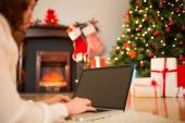 Redhead woman lying on floor using laptop at christmas — Stock fotografie