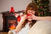 Pretty redhead sitting on couch drinking hot chocolate — Stok fotoğraf