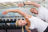 Happy couple stretching hands in yoga class — Stock Photo