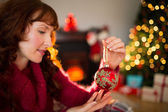 Cheerful redhead holding red bauble  — Stock Photo