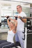 Trainer helping woman with lifting barbell in gym — Stockfoto