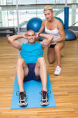 Trainer assisting man with abdominal crunches — Stock Photo
