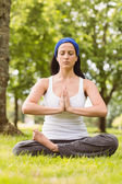 Fit brunette sitting in lotus pose with hands together — Stock Photo