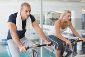 Determined couple working on exercise bikes at gym — Stok fotoğraf