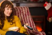 Pretty redhead watching television on couch at christmas — Stock Photo
